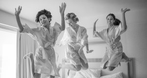 Fun wedding photography the bride and bridesmaids jumping on the bed