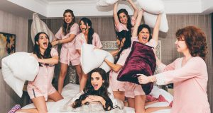 Fun wedding photography pillow fight of the bride and bridesmaids